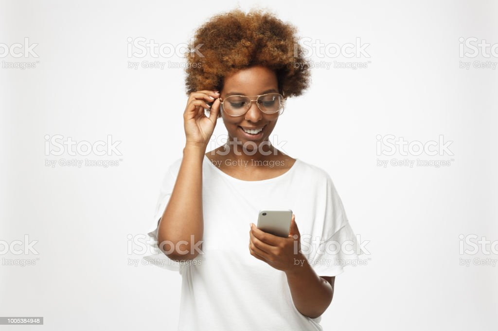 Closeup photo of African American woman standing isolated on gray background looking at screen of cellphone, browsing web pages and smiling nicely while chatting stock photo