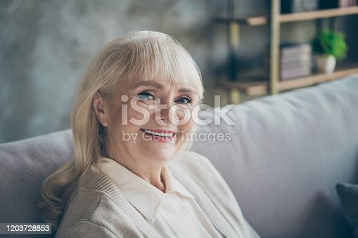 Closeup photo of amazing adorable aged granny homey good mood toothy, beaming smiling sitting comfort sofa divan living room indoors