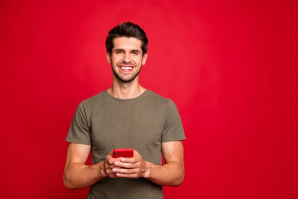 Foto de primer plano de chico increíble sosteniendo las manos de teléfono moderno traje casual aislado en fondo rojo brillante - foto de stock