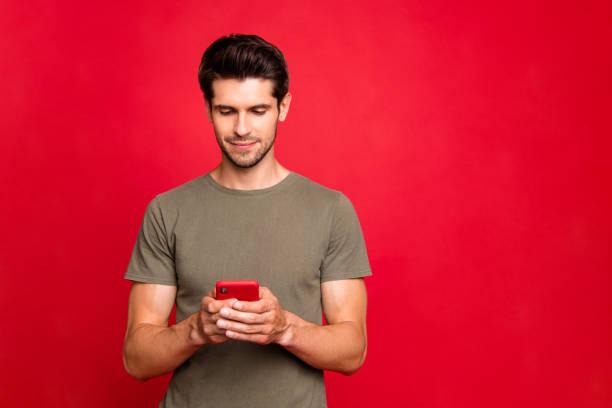Nahaufnahme Foto von erstaunlichen Kerl suchen interessiert Telefon casual Outfit isoliert auf leuchtend roten Hintergrund – Foto
