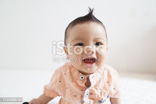 A series of photos of an Asian baby boy with multiple facial expressions including smiling, frowning, curious and big grins.