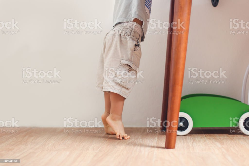 Closeup photo of Asian 18 months / 1 year old toddler baby boy child standing on tiptoes floor at home stock photo