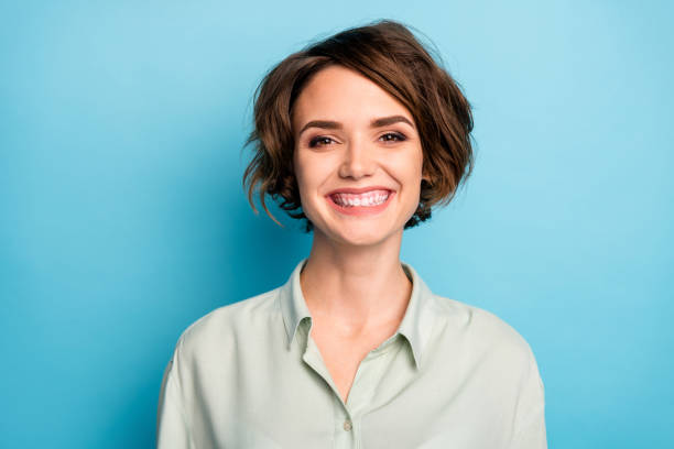Closeup photo of attractive business lady short bob hairstyle smiling beaming good mood responsible person wear casual formalwear green shirt isolated blue color background stock photo