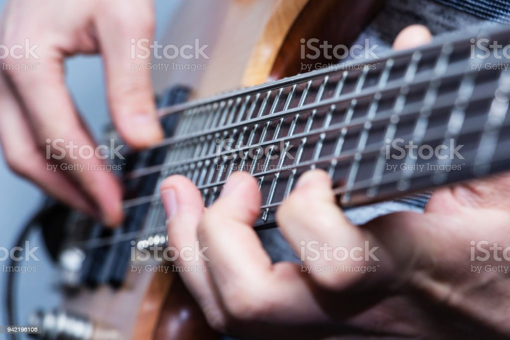 Closeup photo of bass guitar player hands, soft selective focus, live music theme stock photo