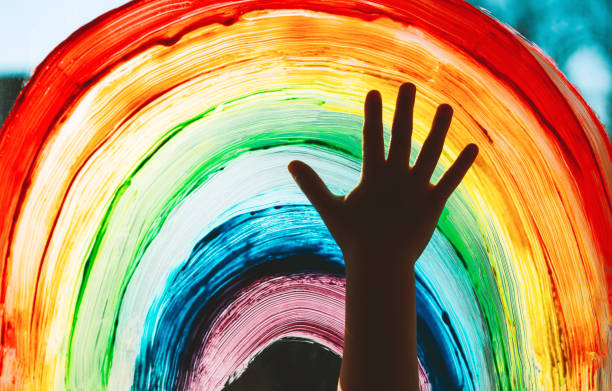 Close-up photo of child's hands touch painting rainbow on window. Family life background. Image of kids leisure at home, childcare, safety joy symbol. stock photo