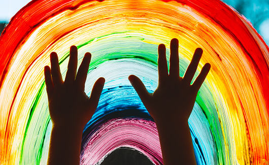 Close-up photo of child's hands touch painting rainbow on window. Family life background. Image of kids leisure at home, childcare, safety joy symbol.