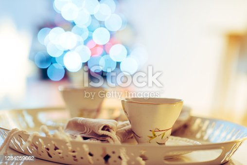 Cozy closeup photo of cups of tee on tray with christmas tree on background