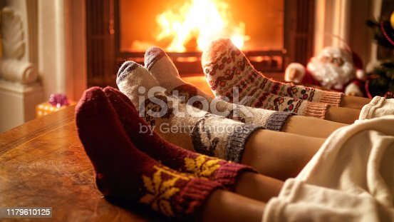istock Closeup photo of family feet in woolen socks lying next to fireplace 1179610125