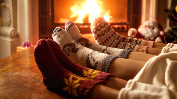 close-up foto van familie voeten in wollen sokken liggend naast open haard - december stockfoto's en -beelden