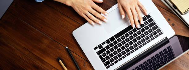 Nahaufnahme Foto von weiblichen Händen mit einem Laptop. Freiberuflerin, die sich über den Computer mit dem Internet verbindet. Blogger oder Journalist, der einen neuen Artikel schreibt. – Foto