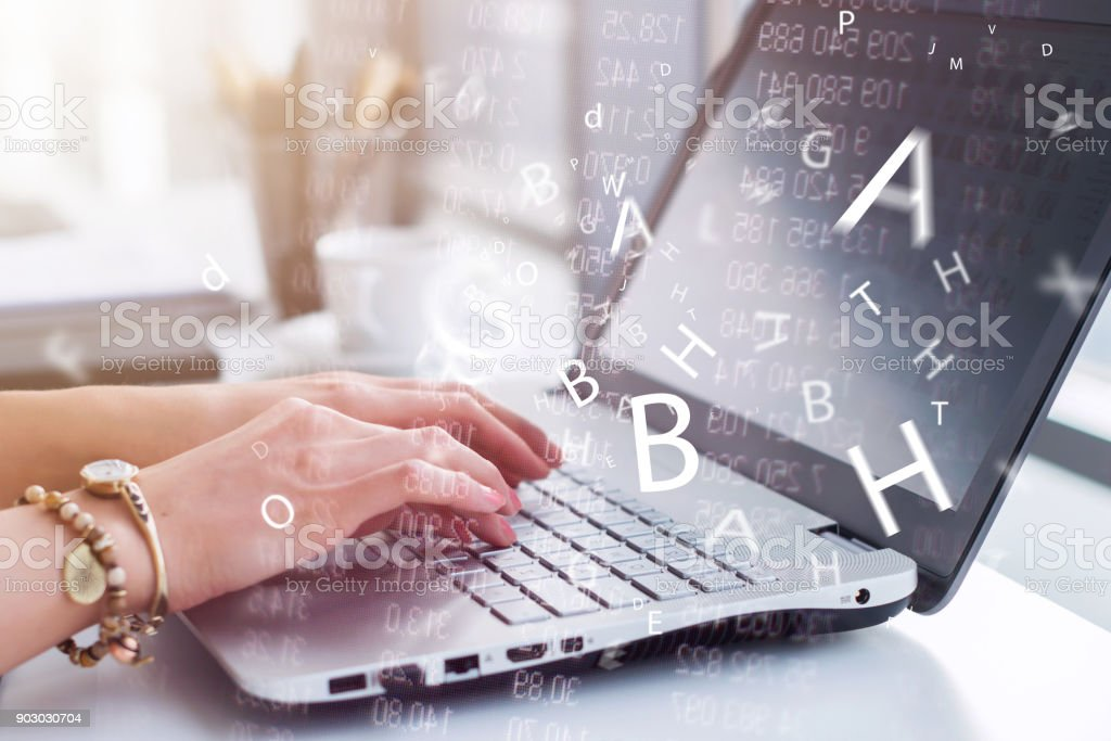 Close-up photo of female hands with accessories working on portable computer in a modern office, using keyboard. stock photo