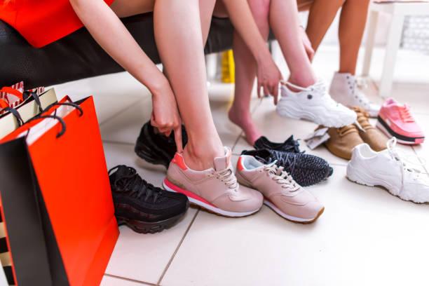 nahaufnahme foto der weiblichen beine auswahl sportschuhe versucht auf verschiedenen turnschuhe in einem einkaufszentrum - neue sneaker stock-fotos und bilder