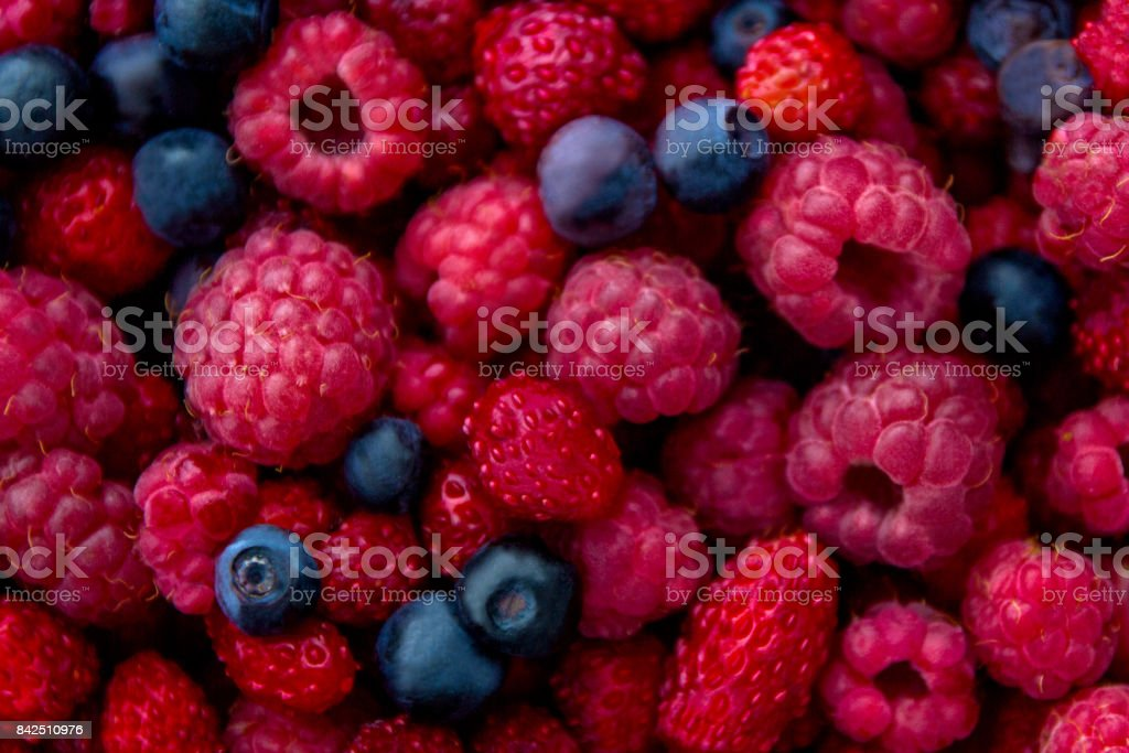 Closeup photo of fresh colorful mix of berries: blueberry, raspberry and wild strawberry - foto stock