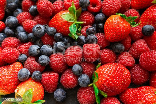 610771802 istock photo Closeup photo of freshly picked berries. On the photo there are a mix of berries: blueberry, wild strawberry and raspberry. Red, blue and purple colors on background 1200121994