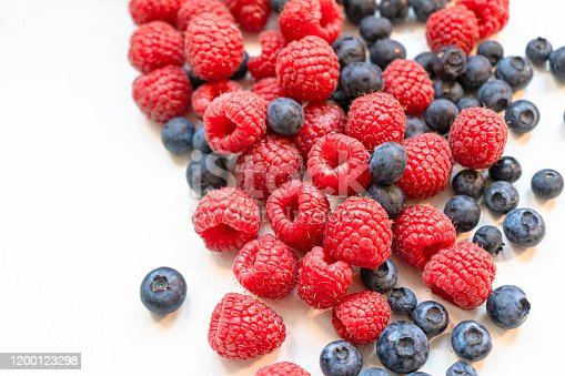 610771802 istock photo Closeup photo of freshly picked berries. On the photo there are a mix of berries: blueberry, wild strawberry and raspberry. Red, blue and purple colors on background 1200123298