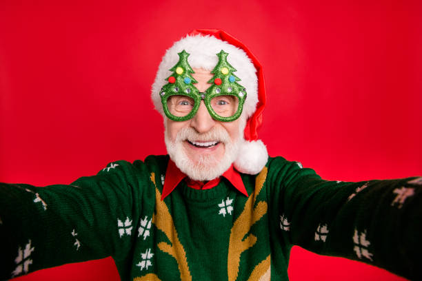 Closeup photo of funny aged santa claus role man making crazy selfies wear x-mas tree shape specs knitted sweater hat isolated red background Closeup photo of funny aged santa claus role man making crazy selfies, wear x-mas tree shape specs knitted sweater hat isolated red background funny christmas stock pictures, royalty-free photos & images