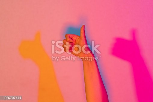A close-up photo of a hand lit by neon lights doing thumbs up.