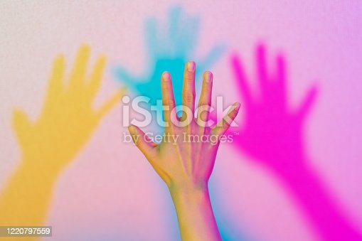 A close-up photo of a hand lit by neon lights.