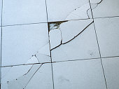 Close-up view of light gray tile with large diagonal cracks and chips.
