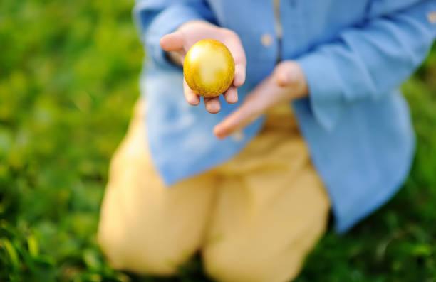 Foto primer plano del niño, la caza de huevos de Pascua en el parque de la primavera en el día de Pascua - foto de stock