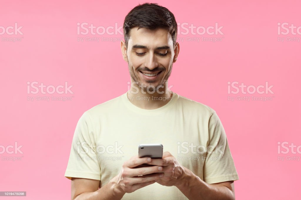 Closeup photo of man in beige tshirt standing isolated on pink background looking attentively at screen of cellphone, browsing web pages and smiling nicely while chatting with friends stock photo