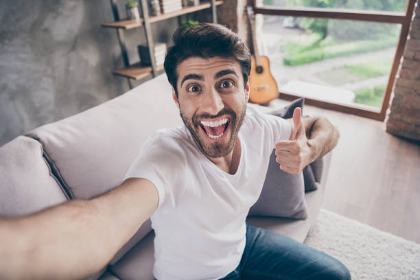 Closeup photo of mixed race arab guy sitting cozy sofa making selfies raising thumb up expressing agreement excited wear casual outfit flat loft living room indoors stock photo