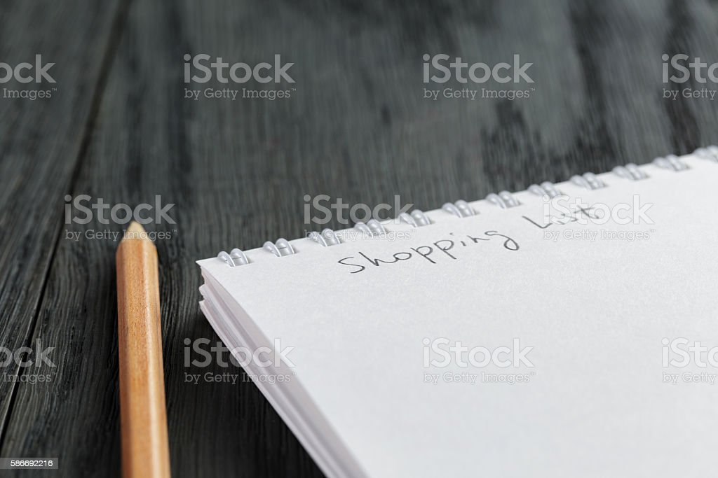 closeup photo of open empty notepad with shopping list phrase stock photo