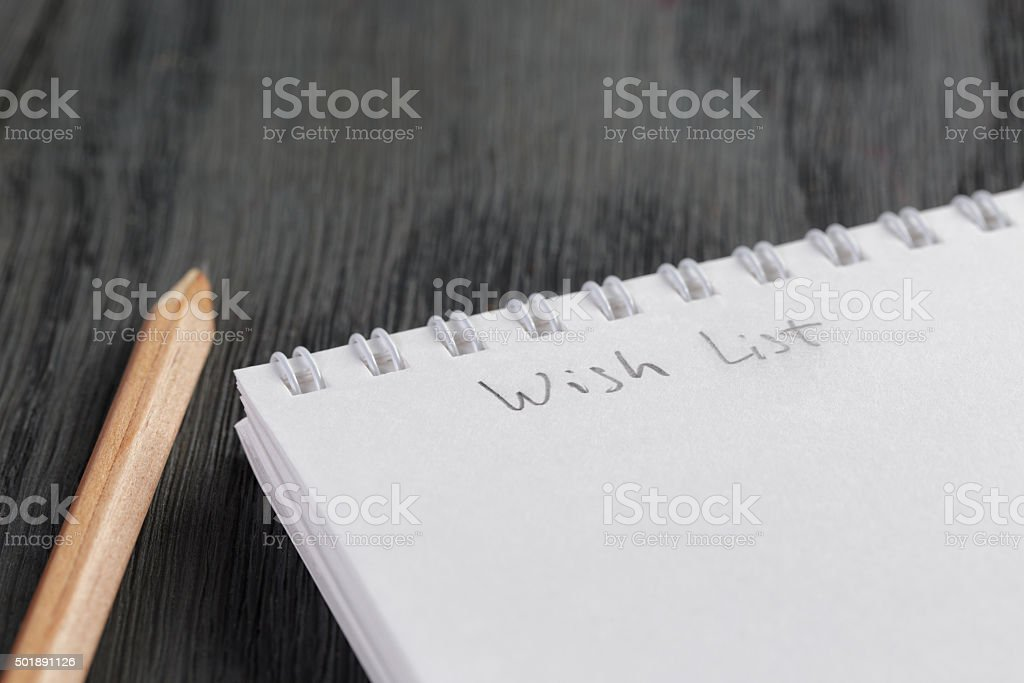 closeup photo of open empty notepad with wish list phrase stock photo