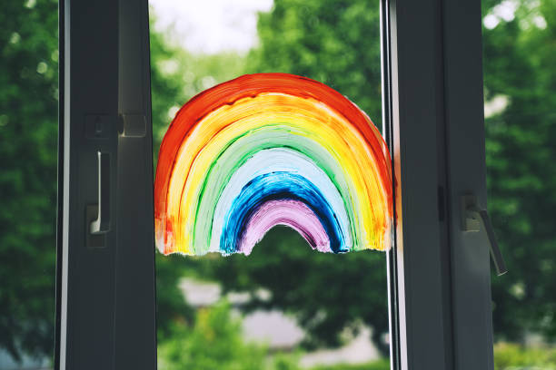 Close-up photo of painting rainbow on window. stock photo