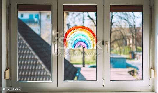 Close-up photo of painting rainbow on window. Rainbow painted with paints on glass is a symbol for many meanings.