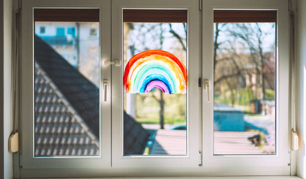 Close-up photo of painting rainbow on window. Rainbow painted with paints on glass is a symbol for many meanings. stock photo