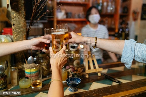 A group pf people are social gathering and cheering with beer in a bar. The bar owner is wearing protective face mask to prevent avian illness spread.