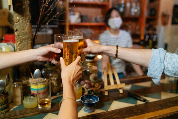 Close-up photo of people cheering with beer in bar with illness prevention protection measures are taken stock photo