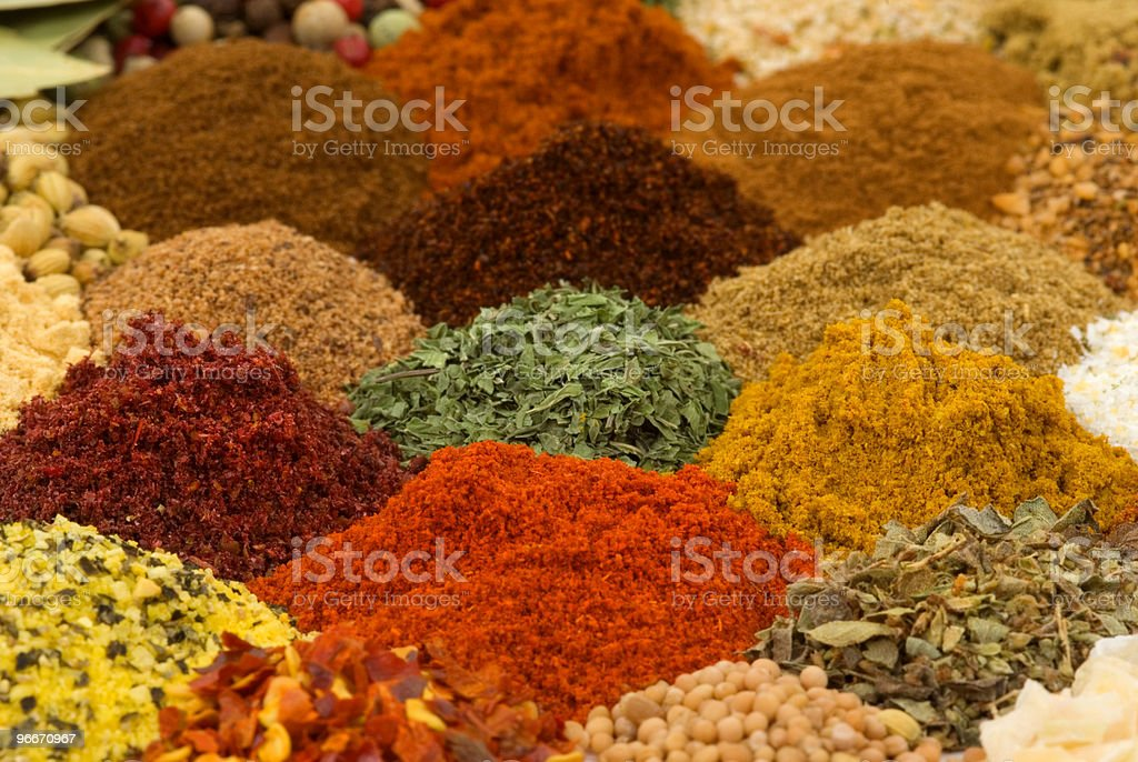 Close-up photo of piles of a variety of spices and herbs royalty-free stock photo