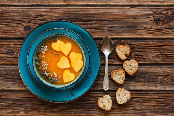 Foto de close-up de placa com sopa creme abóbora caseira fresca com sementes e brindes de forma de coração com fundo de madeira vintage. - foto de acervo