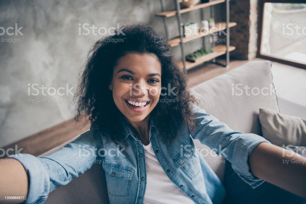 Close-upfoto van vrij grappige donkere huid krullende blogger dame die selfies opgewekte toothy glimlachende sociale netwerkblogger comfortabele laag toevallige denimuitrustingwoonkamer binnen maakt - Royalty-free Afro Stockfoto