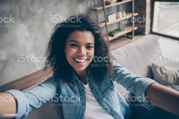 Closeupfoto Van Vrij Grappige Donkere Huid Krullende Blogger Dame Die Selfies Opgewekte Toothy Glimlachende Sociale Netwerkblogger Comfortabele Laag Toevallige Denimuitrustingwoonkamer Binnen Maakt Stockfoto en meer beelden van Afro