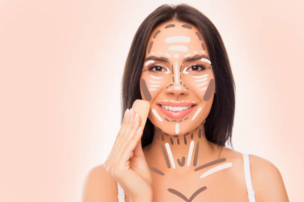 close-up photo of pretty smiling woman with sponge doing professional contouring face make-up sample stock photo