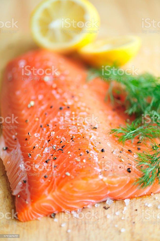 Closeup photo of raw filet of salmon with salt, lemon, dill stock photo
