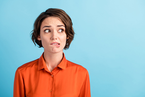 Closeup photo of sad depressed displeased lady horrified facial expression, made huge big mistake feel guilty look side empty space bite lips wear orange shirt isolated blue color background