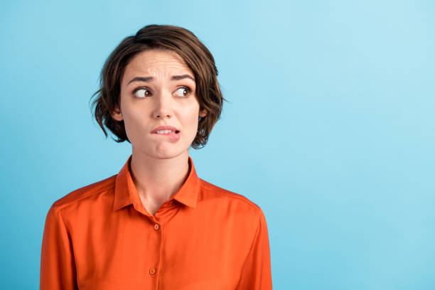 Closeup photo of sad depressed displeased lady horrified facial expression made huge big mistake feel guilty look side empty space bite lips wear orange shirt isolated blue color background stock photo