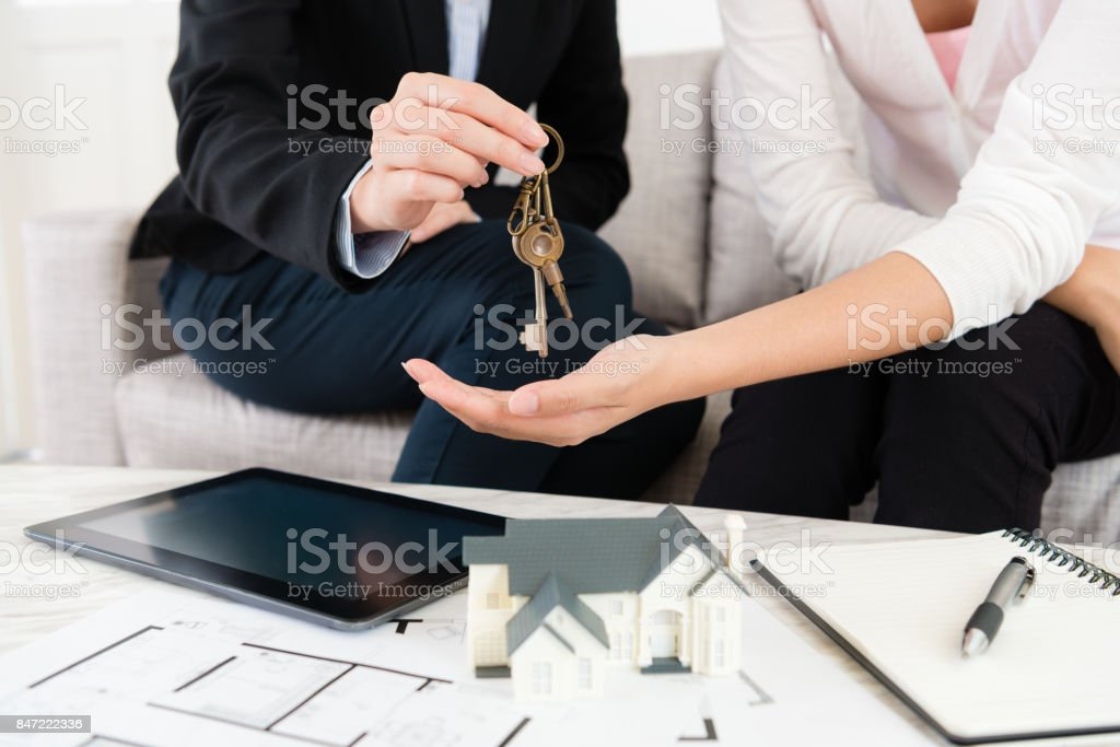 closeup photo of saleswoman giving house key stock photo