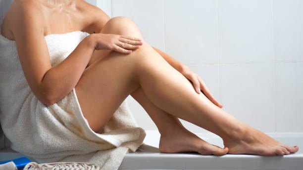 nahaufnahme foto sexy junge frau in badetuch sitzen im bad - bein make up stock-fotos und bilder