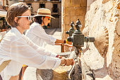 Closeup photo of two woman friends washing hands and drinking water from a city fountain