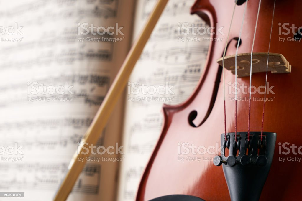 Close-up photo of vintage violin with bow and musical notes. Cello or...