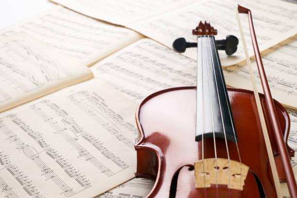 nahaufnahme foto von vintage violine mit bogen und musiknoten. - philharmonie stock-fotos und bilder