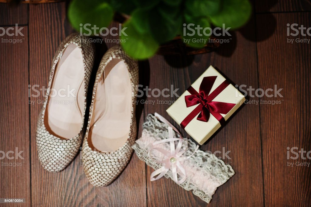 Close-up photo of wedding shoes, garter and tiny box with red ribbon. stock photo