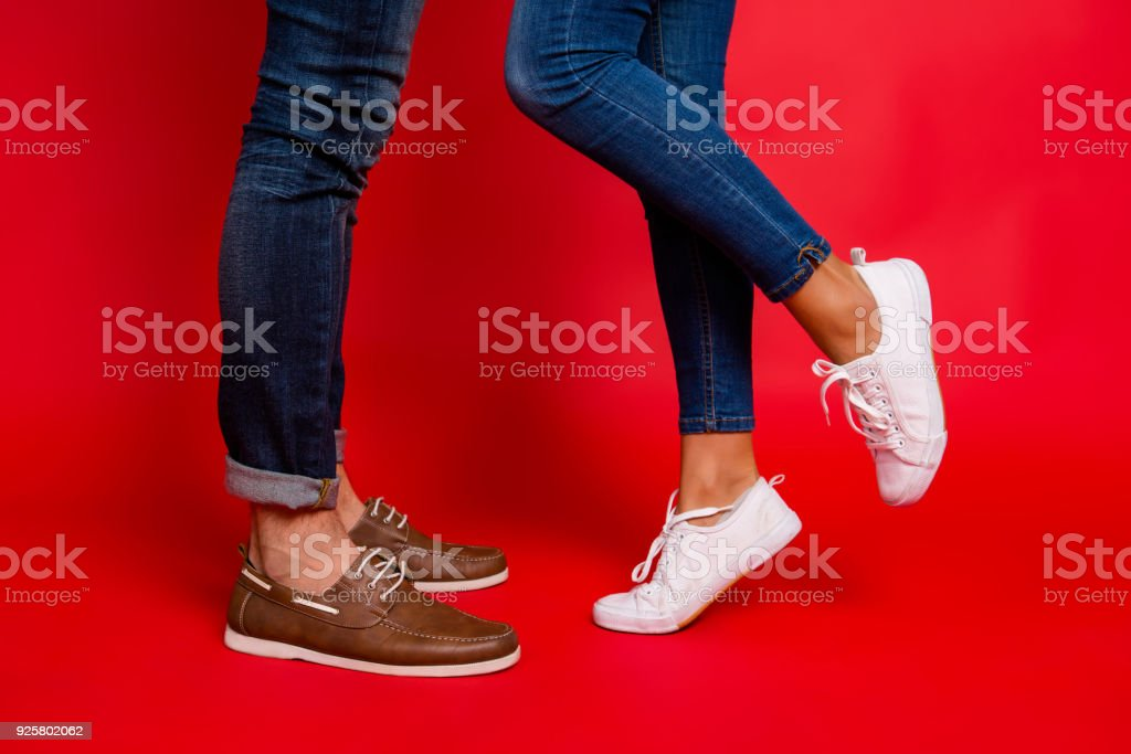 aa29813ad Closeup photo of woman and man legs in jeans, pants and shoes, girl with  raised leg, stylish couple kissing during date, isolated over red  background, ...