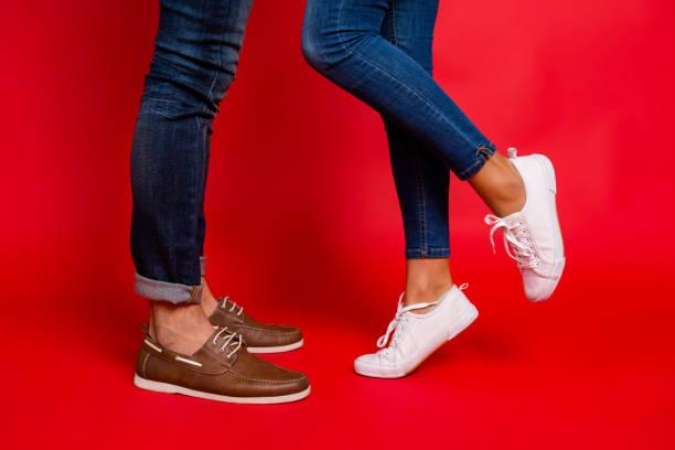 close-up foto van vrouw en man benen in jeans, broek en schoenen, meisje met opgeheven been, stijlvolle paar zoenen tijdens datum, geïsoleerd op rode achtergrond, hij vs ze - shoe stockfoto's en -beelden