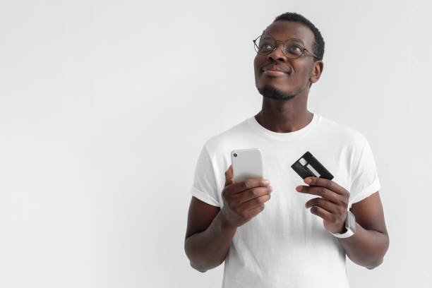 Closeup photo of young African male in eyeglasses pictured isolated on gray background thinking and dreaming about pleasant plans with credit card and smartphone in hands, ready to purchase in web stock photo